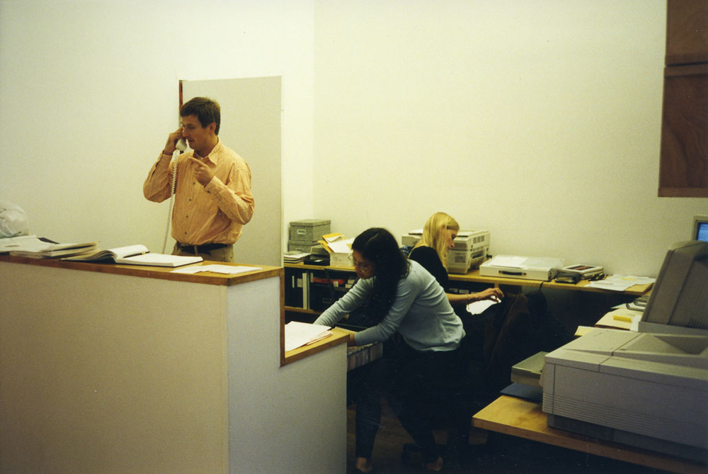 A photograph of David Zwirner, Hanna Schouwink, and Angela Choon at the front desk of 43 Greene Street in New York, circa 1997.