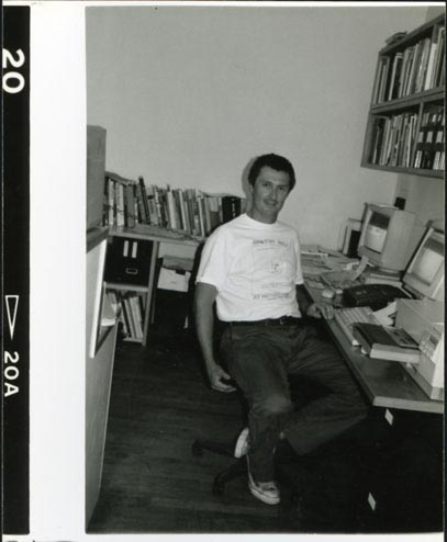 David Zwirner, wearing a Raymond Pettibon T-shirt, at the front desk of 43 Greene Street in New York, circa 1997.