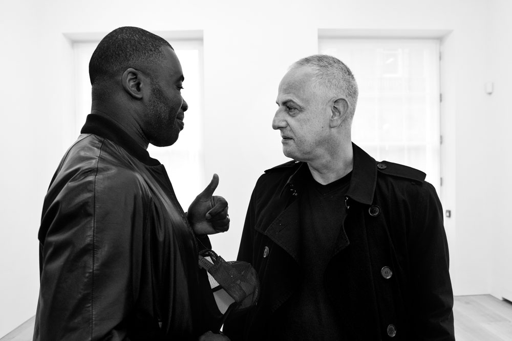 Chris Ofili and Luc Tuymans in conversation during the installation of the exhibition  Luc Tuymans: Allo! at 24 Grafton Street in London, dated 2012.