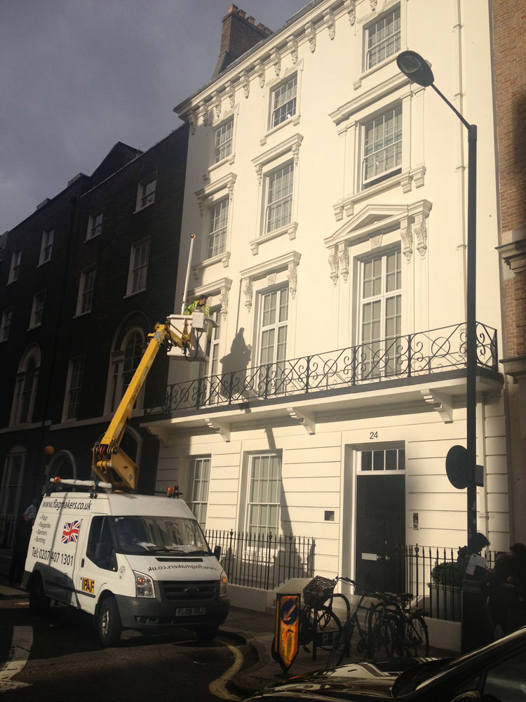 A photograph of the finishing touches: the David Zwirner flag being added to 24 Grafton Street in London, dated 2012.