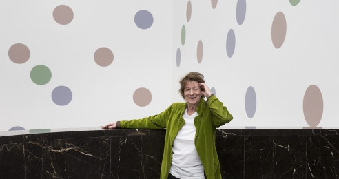 A photograph of Bridget Riley in front of her mural titled Messengers at The National Gallery in London, dated 2018.