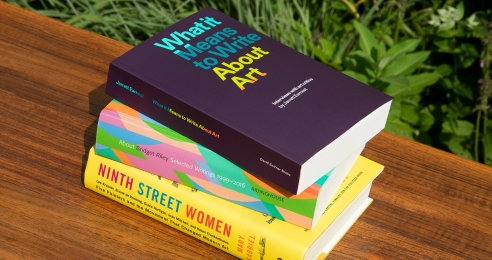 A photograph of three books stacked on a bench outside. The titles are: What it Means to Write About Art: Interviews with art critics; About Bridget Riley: Selected Writings 1999–2016; Ninth Street Women: Lee Krasner, Elaine De Kooning, Grace.